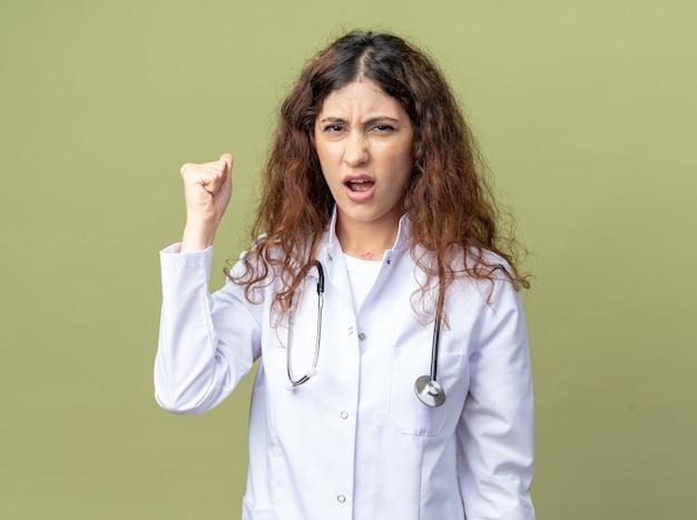 Jovem médica carrancuda vestindo túnica médica e estetoscópio olhando para frente fazendo um gesto forte isolado na parede verde oliva