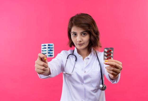 Jovem médica com jaleco branco com estetoscópio mostrando bolha com comprimidos em pé sobre a parede rosa
