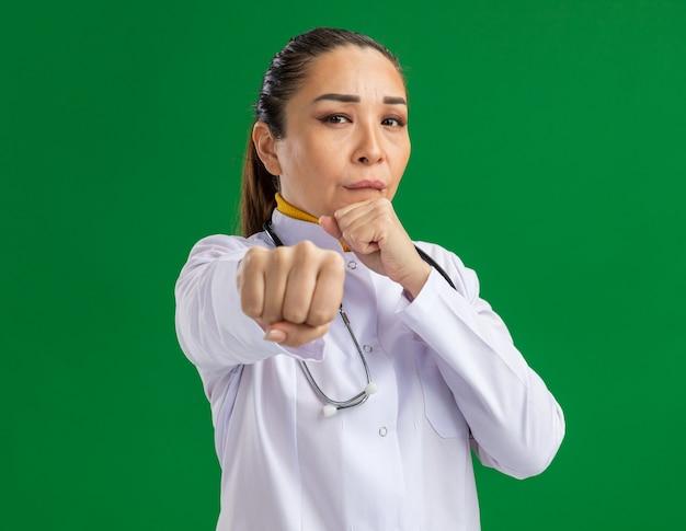 Jovem médica com jaleco branco com estetoscópio no pescoço e rosto sério, posando como um boxeador com os punhos cerrados em pé sobre a parede verde