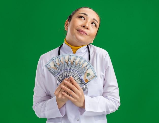 Jovem médica com jaleco branco com estetoscópio no pescoço, olhando feliz e satisfeita em pé sobre a parede verde