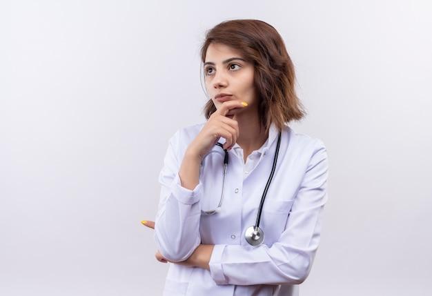 Jovem médica com jaleco branco com estetoscópio olhando para o lado com a mão no queixo e expressão pensativa no rosto pensando