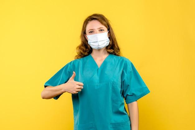 Jovem médica com máscara no espaço amarelo de frente