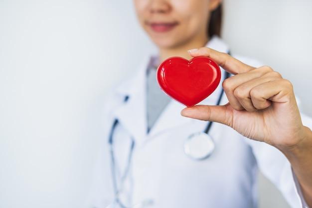 Jovem médica com o estetoscópio segurando coração vermelho, conceito de cuidados saudáveis de cardiologista