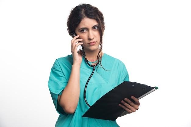 Jovem médica com prancheta e falando no celular sobre fundo branco