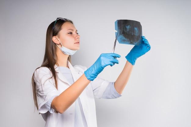 Jovem médica com um jaleco branco e luvas azuis examina um raio-x