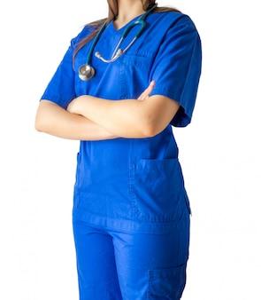 Jovem médica com um uniforme azul de médico em pé com confiança e as mãos cruzadas