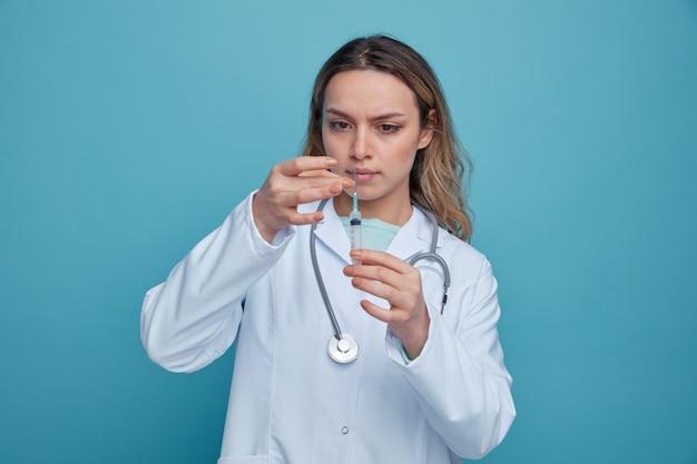 Jovem médica concentrada usando túnica médica e estetoscópio em volta do pescoço batendo seringa para remover bolhas de ar dela