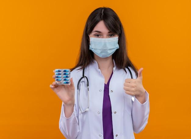 Jovem médica confiante com túnica médica com estetoscópio e máscara facial descartável contém remédios e polegares para cima em um fundo laranja isolado com espaço de cópia
