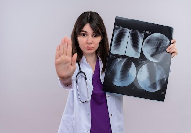 Jovem médica confiante em roupão médico com estetoscópio segura uma foto de raio-x e gestos param em um fundo branco isolado com espaço de cópia