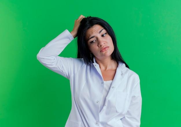 Jovem médica confusa usando manto médico, olhando para o lado tocando a cabeça