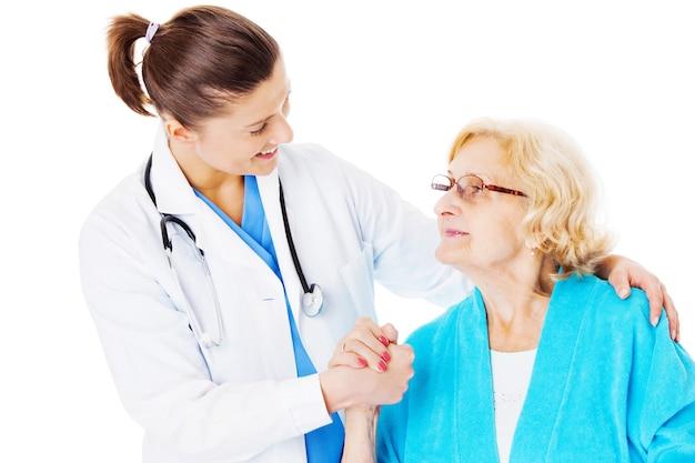 Jovem médica consolando mulher idosa isolada sobre fundo branco