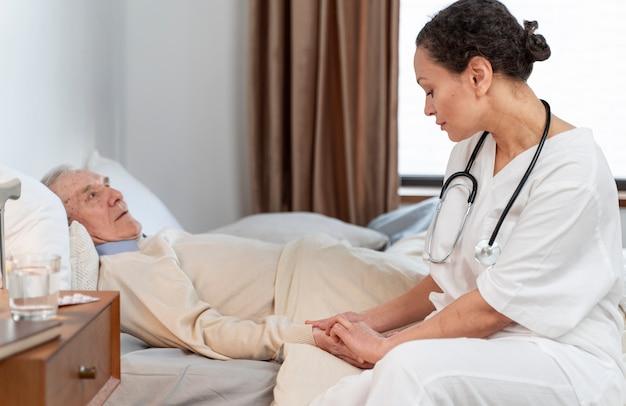 Jovem médica conversando com seu paciente sênior