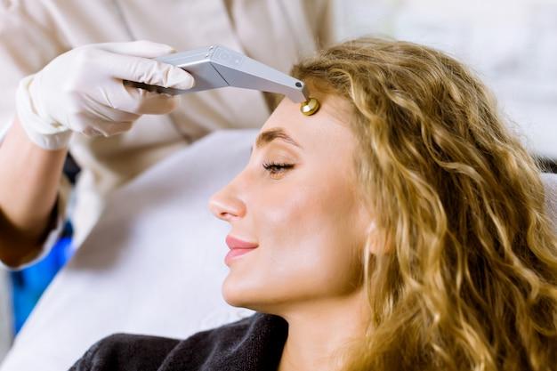 Jovem médica-cosmetologista faz o procedimento de microdermoabrasão da pele facial de uma mulher jovem e bonita na clínica de cosmetologia.