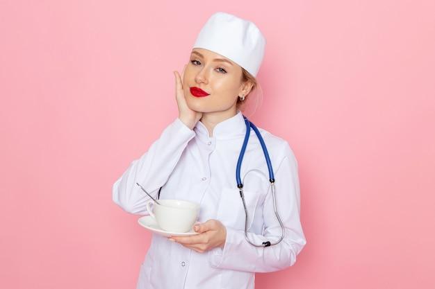 Jovem médica de terno branco com estetoscópio azul segurando a xícara de café de frente para o trabalho