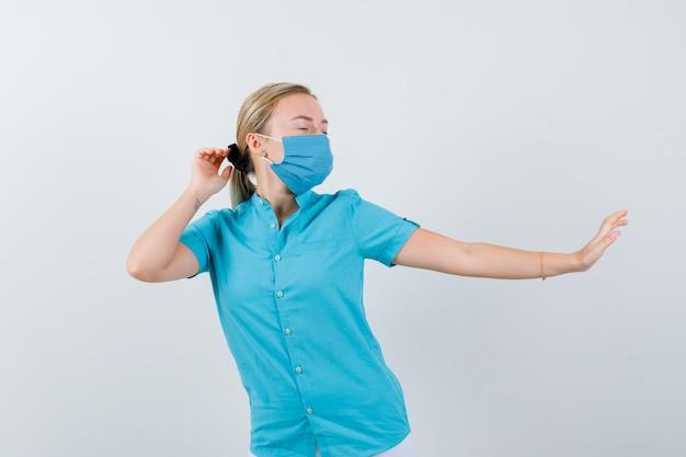 Jovem médica de uniforme mostrando gesto de pare e parecendo animada