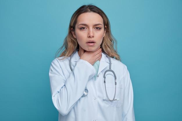 Jovem médica dolorida, vestindo bata médica e estetoscópio ao redor do pescoço, segurando a garganta