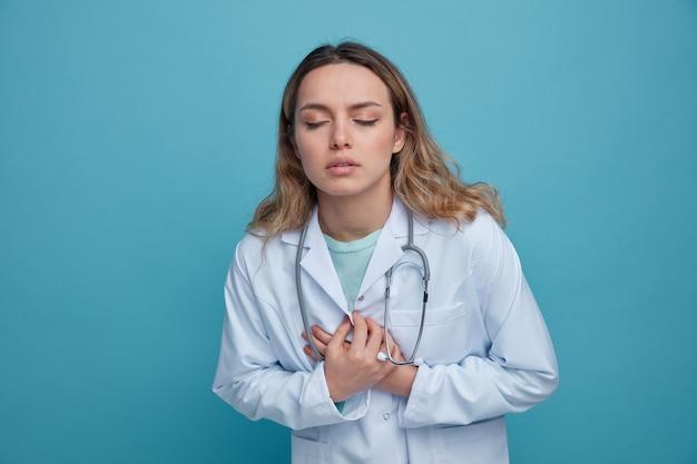 Jovem médica dolorida, vestindo bata médica e estetoscópio no pescoço, mantendo as mãos no peito com os olhos fechados