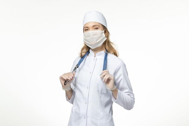 Jovem médica em terno médico, vista frontal, usando máscara protetora devido a coronavírus na mesa branca