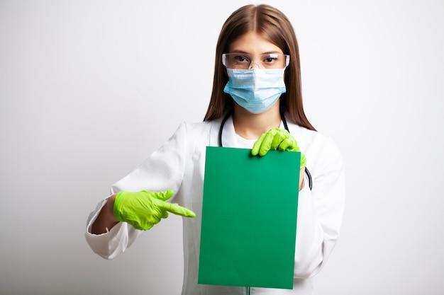 Jovem médica em uma máscara detém uma folha de papel em branco