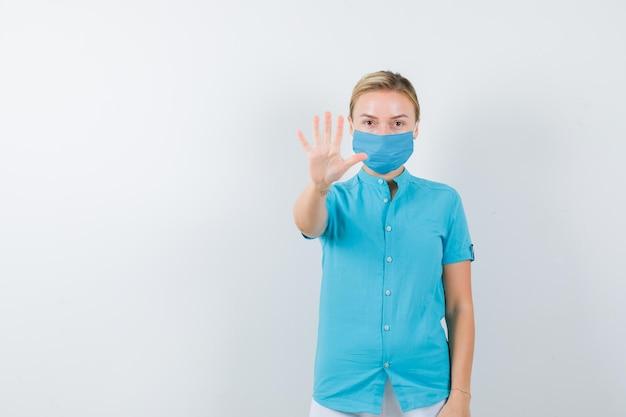 Jovem médica em uniforme médico, máscara mostrando gesto de parada e olhando séria