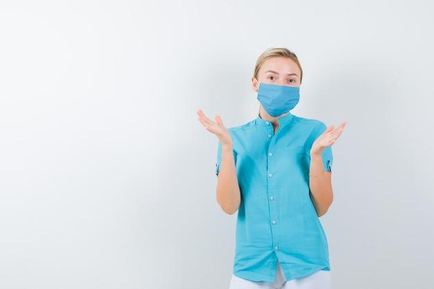 Jovem médica espalhando as palmas das mãos em uniforme médico, máscara e parecendo confiante