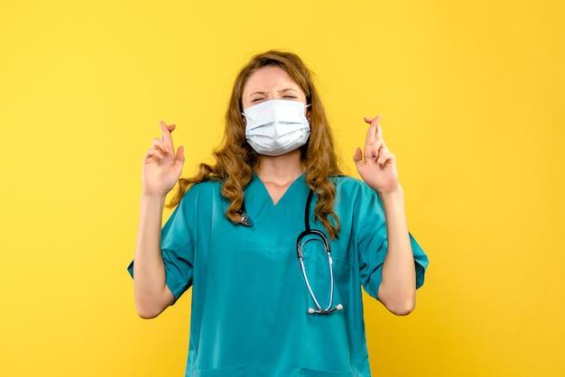 Jovem médica esperando na máscara no espaço amarelo de frente