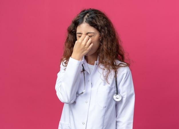 Jovem médica estressada usando roupão médico e estetoscópio segurando o nariz com os olhos fechados, isolado na parede rosa com espaço de cópia