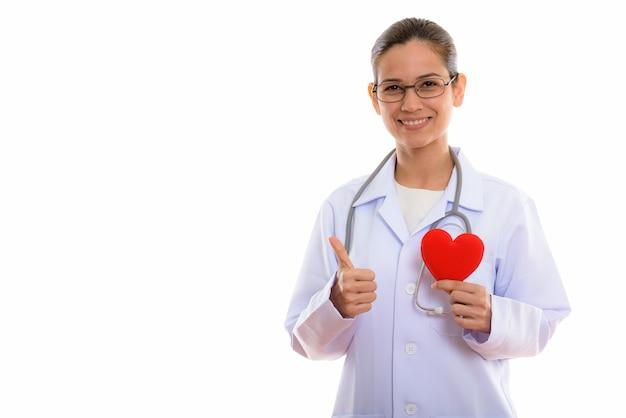 Jovem médica feliz sorrindo enquanto segura um coração vermelho