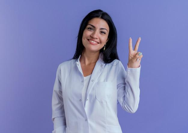Jovem médica feliz vestindo túnica médica, olhando para fazer o sinal da paz
