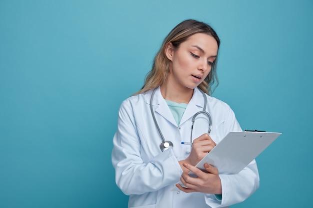 Jovem médica impressionada usando túnica médica e estetoscópio em volta do pescoço, escrevendo com uma caneta na prancheta