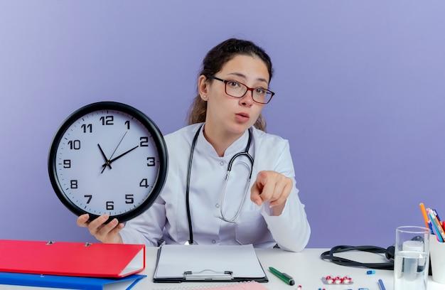 Jovem médica impressionada usando túnica médica e estetoscópio, sentada à mesa com ferramentas médicas, segurando um relógio, olhando e apontando isolado