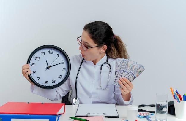 Jovem médica impressionada usando túnica médica, estetoscópio e óculos, sentada na mesa com ferramentas médicas, segurando dinheiro e relógio e olhando para o relógio isolado