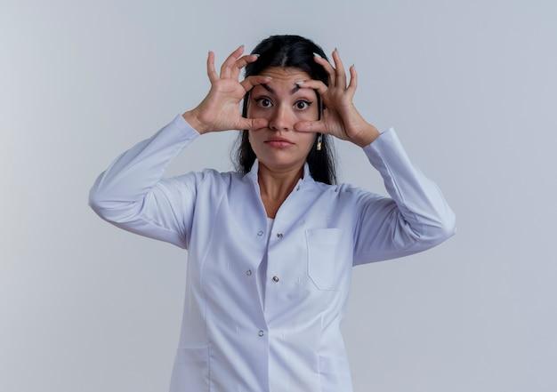 Jovem médica impressionada usando túnica médica, parecendo fazendo grandes olhos isolados