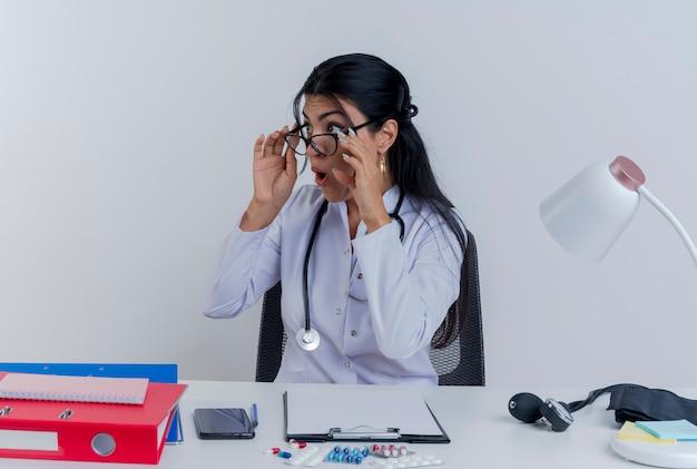 Jovem médica impressionada vestindo túnica médica, estetoscópio e óculos, sentada à mesa com ferramentas médicas, olhando para o lado e segurando os óculos isolados