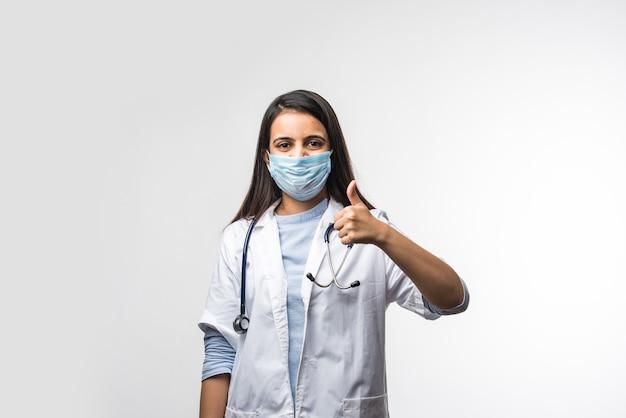 Jovem médica indiana com uniforme e máscara mostrando sucesso de polegar para cima