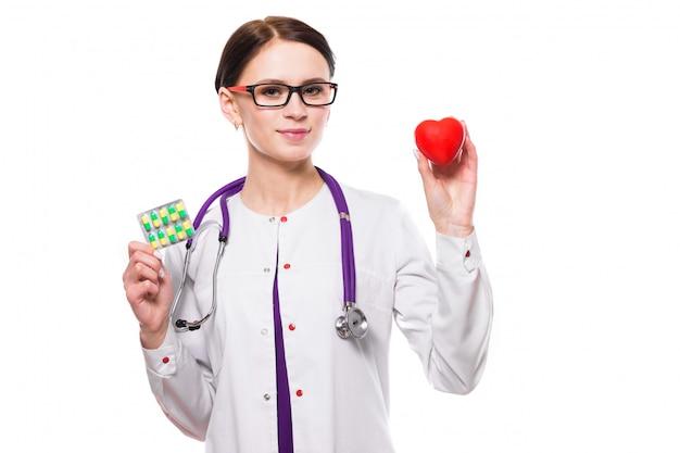 Jovem médica linda segurando coração e comprimidos nas mãos no fundo branco