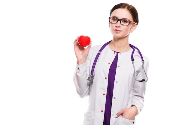 Jovem médica linda segurando o coração na mão no fundo branco