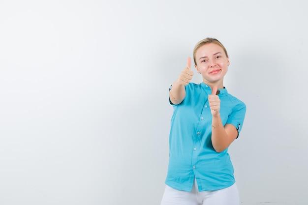 Jovem médica mostrando os polegares em uniforme médico, máscara e olhando positiva