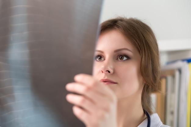 Jovem médica olhando para a imagem de raio-x dos pulmões. saúde e conceito médico