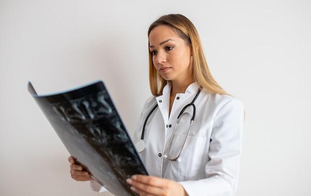 Jovem médica, olhando para a imagem de raio-x em seu escritório