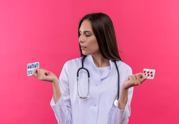 Jovem médica pensando em um estetoscópio jaleco e olhando os comprimidos na mão na parede rosa isolada