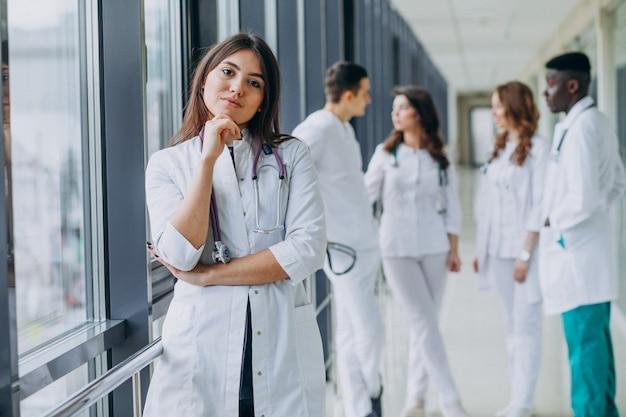 Jovem médica posando no corredor do hospital