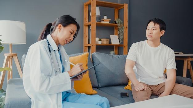 Jovem médica profissional da ásia usando tablet digital, compartilhando boas notícias de testes de saúde com paciente feliz do sexo masculino sentado no sofá em casa