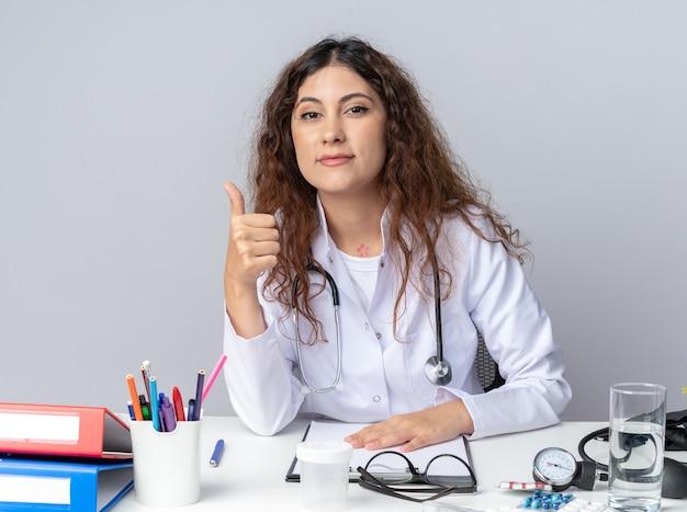 Jovem médica satisfeita vestindo túnica médica e estetoscópio sentada à mesa com ferramentas médicas, mantendo a mão na mesa, olhando para a frente, mostrando o polegar isolado na parede branca
