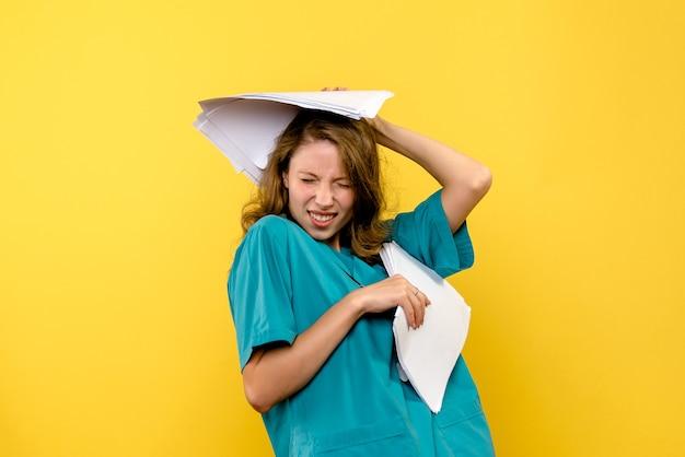 Jovem médica segurando arquivos no espaço amarelo de frente