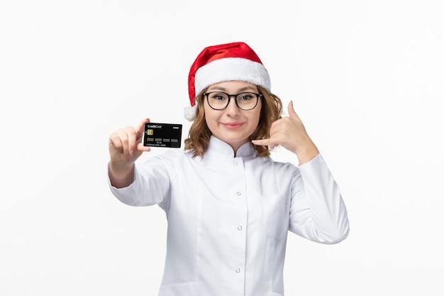 Jovem médica segurando um cartão de banco na parede branca enfermeira de dinheiro de frente para ano novo