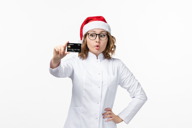Jovem médica segurando um cartão de banco na parede branca, enfermeira, feriado, vista frontal, ano novo