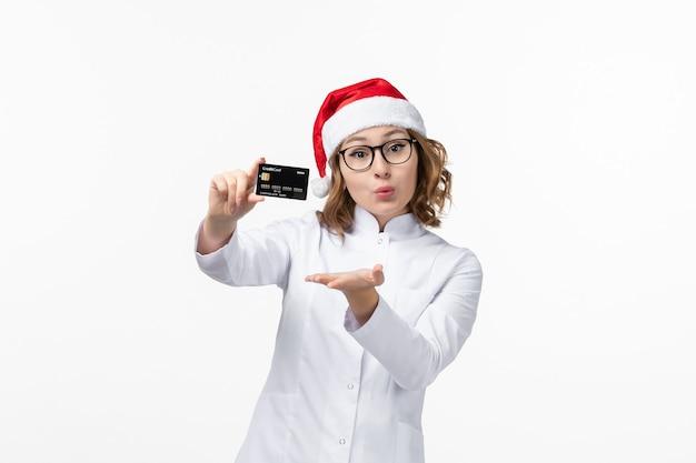 Jovem médica segurando um cartão do banco na parede branca.