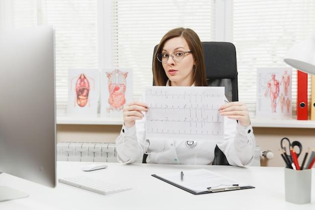 Jovem médica sentada à mesa com documentos médicos, registro de eletrocardiograma, gráfico de eletrocardiograma de eletrocardiograma de coração e eletrocardiograma de onda em papel no escritório de luz no hospital