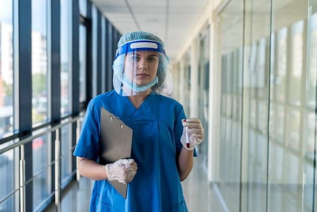 Jovem médica séria usando protetor facial e observando sangue positivo para o resultado covid-19. estudante estagiário segurando um tubo de ensaio no hospital
